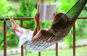 8581034 - young woman reading a book lying in a hammock